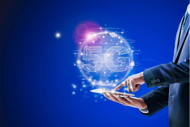 En man som håller i en smartphone och en illustration ovanför som illustrerar 5G