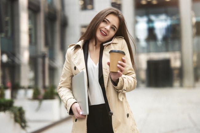 kvinnla håller i papper och kaffemugg medan hon pratar i telefon och går längs gata