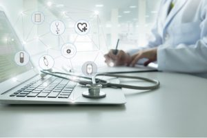 laptop med stetoskop på och en antecknande läkare i bakgrunden