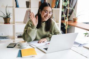 kvinna vid skrivbord vinkar till någon på en laptopskärm