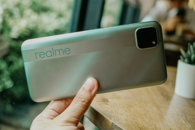 hand håller i en mobiltelefon med märket Realme på baksidan