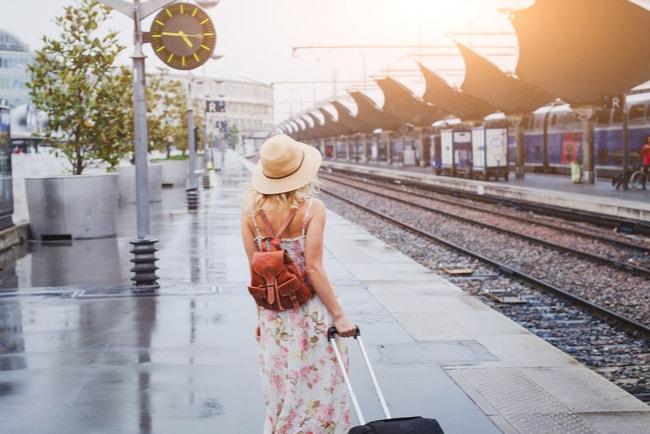 kvinna med bagage vid tågstation