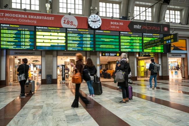 människor framför tavlor med avgångar inne på Stockholms centralstation
