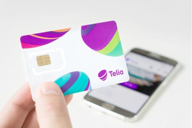 hand håller i nytt simkort från Telia, smartphone i bakgrunden