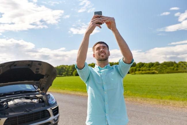 man med bil håller upp telefonen och söker efter täckning