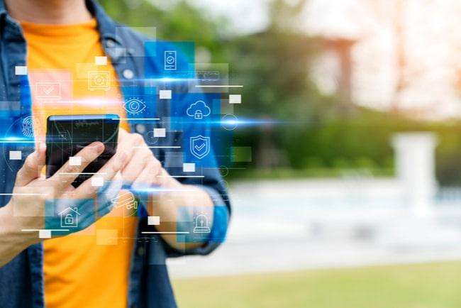närbild på person som håller i smartphone utomhus, internet of things-symboler