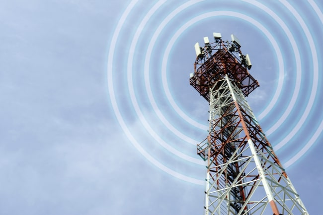 mobilmast skickar ut signaler mot blå himmel i bakgrunden