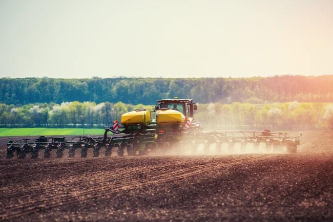 Traktor plöjer ett odlingsfält.